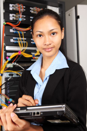 Woman with tablet standing near network rack